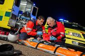 stock photo of stretcher  - Paramedics giving first - JPG
