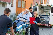 stock photo of stretcher  - Emergency team assisting injured elderly man lying on stretcher outdoors - JPG
