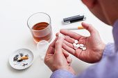 stock photo of hangover  - Man addicted to pills and alcohol and cigarettes