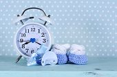 stock photo of teething baby  - Baby boy nursery blue and white booties and clock on aqua vintage shabby chic wood table and polka dot background for baby shower or newbornl greeting card - JPG