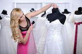 stock photo of dress mannequin  - Designer wedding dresses measures the dress on a mannequin in her shop - JPG