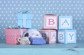foto of girlie  - Baby nursery bootie dummy pacifier and baby letters pink and blue gift boxes against a vintage aqua blue table and polka dot background for baby shower or newborn girl greeting card - JPG