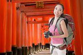 pic of inari  - Happy smiling Asian young female backpacker with camera in Fushimi Inari Taisha - JPG