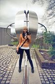 picture of longitude  - Smiling young woman tourist straddling the prime meridian line for zero degrees longitude at greenwich - JPG