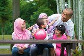 foto of southeast asian  - Happy Southeast Asian family sitting at garden bench having fun - JPG