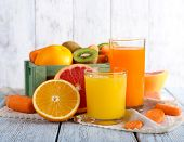stock photo of fruit-juice  - Fruit and vegetable juice in glasses and fresh fruits in box on wooden table on wooden wall background - JPG