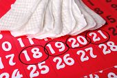 picture of menses  - Sanitary pads on red calendar background - JPG