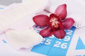 picture of menses  - Sanitary pads and lilac orchid on blue calendar background - JPG