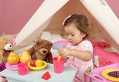 stock photo of teepee  - Happy toddler girl engaged in pretend play tea party indoors at home with a teepee tent - JPG