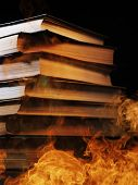 picture of hardcover book  - Conceptual image of a tall stack of hardcover books in a burning fire with flames and smoke swirling around them in a darkened room with copyspace - JPG