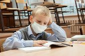 foto of epidemic  - School children in medical face mask are learning in the half empty classroom during epidemic of flu - JPG