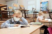 pic of epidemic  - School children in medical face mask are learning in the half empty classroom during epidemic of flu - JPG