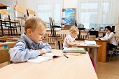 stock photo of epidemic  - School children are learning in the half empty classroom during epidemic of flu - JPG