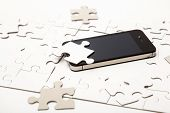 stock photo of assemblage  - White puzzle with mobile phone on the table - JPG