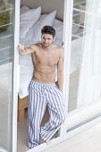 picture of partially nude  - Full length of shirtless young man standing at balcony doorway - JPG