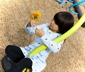 GIRL PLAYING WITH FLOWERS ON PLAYGROUND