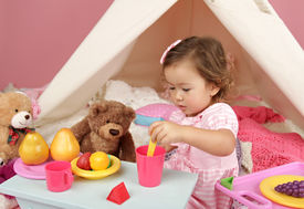 stock photo of girlie  - Happy toddler girl engaged in pretend play tea party indoors at home with a teepee tent - JPG