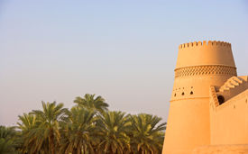 pic of oasis  - A beautifully decorated tower at Al Khandaq Castle one of several castles in the verdant oasis town of Al Buraymi in the Sultanate of Oman. A palm oasis can be seen in