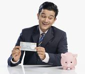 stock photo of indian currency  - Businessman holding currency note and looking at piggy bank - JPG