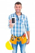 pic of handyman  - Portrait of smiling handyman showing mobile phone on white background - JPG