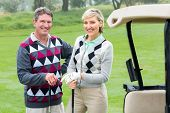 stock photo of beside  - Happy golfing couple with golf buggy beside on a foggy day at the golf course - JPG