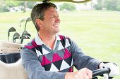 stock photo of buggy  - Happy golfer driving his golf buggy on a sunny day at the golf course - JPG