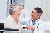 stock photo of male face  - Happy male doctor looking at female patient in clinic - JPG