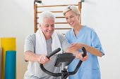 picture of exercise bike  - Senior man doing exercise bike with therapist in fitness studio - JPG