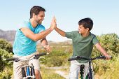 picture of exercise bike  - Father and son on a bike ride on a sunny day - JPG