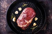 picture of ribeye steak  - Raw fresh uncooked meat Steak Ribeye on grill iron pan on dark background - JPG