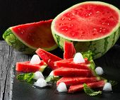picture of watermelon slices  - Seedless ripe watermelon cut slices with mint and ice on a black background - JPG