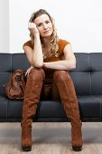 pic of woman boots  - woman wearing brown clothes and boots with a handbag sitting on sofa - JPG