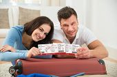 stock photo of boarding pass  - Portrait Of Happy Young Couple Packing Luggage Showing Boarding Pass - JPG