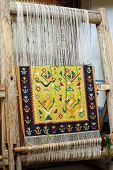 stock photo of loom  - vintage wooden loom with half knit colored carpet on threads - JPG