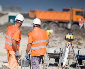 stock photo of geodesic  - Two construction workers standing on building site truck in background - JPG
