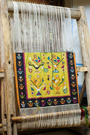 picture of handloom  - vintage wooden loom with half knit colored carpet on threads - JPG
