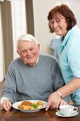 picture of meals wheels  - Senior Man Being Served Meal By Carer - JPG