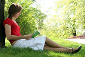 picture of young women  - Portrait of a young woman reading book in the park - JPG