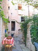 Small Provencal City Path With Chairs And A Coloured Table, Azur Coast, South Of France poster
