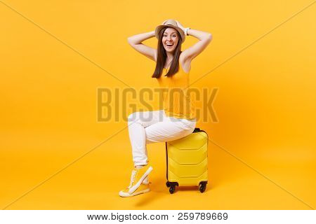 poster of Traveler Tourist Woman In Summer Casual Clothes, Hat Sit On Suitcase Isolated On Yellow Orange Backg