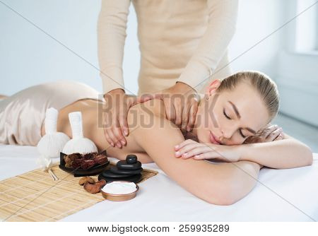 poster of Masseur doing massage on woman body in the spa salon. Girl gets spa procedure. Beauty treatment conc
