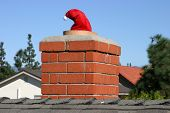 image of 24th  - Santa Claus goes down a chimney with only his hat left showing - JPG