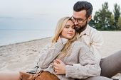 Affectionate Couple In Autumn Outfit Sitting And Hugging On Beach poster