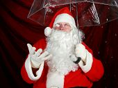 pic of 24th  - Santa Claus holds his transparent umbrella and checks for signs of snow before he goes to work on December 24th Christmas Eve - JPG
