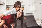 Mother And Daughter Doing Piggyback In Funny Gesture Emotion At Home. Young Sister Playing With Girl poster