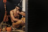 Halloween Spirit And Supernatural Concept. Macho In Witch Hat And Bared Torso Sitting On Floor. Man  poster