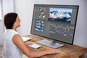 Female Editor Editing Video On Computer Over Wooden Desk poster