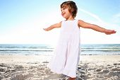 stock photo of cute little girl  - Small cute girl in white dress enjoying sunny day at the beach - JPG