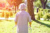 Asian Senior Or Elderly Old Lady Woman Use Walker With Strong Health While Walking At Park In Happy  poster