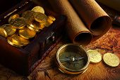 stock photo of treasure chest  - Old brass compass lying on a very old map with treasure chest full of golden coins - JPG